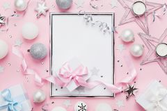 Frame with holiday balls, gift box and sequins on stylish pink table top view. Fashion christmas background. Flat lay. royalty free stock photography
