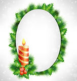 Frame with holly, pine and candle on grayscale. Candle, holly sprigs and pine branches with grayscale blank oval frame in snowfall on grayscale background Stock Photography