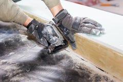 Frame house wall construction. Worker attach a vapor barrier with staple gun. Stock Image