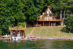 A-Frame House on Water with Boats. A beautiful A-Frame waterfront home with boat house, boats and jet skis on the shore Virginia's Smith Mountain Lake royalty free stock photo