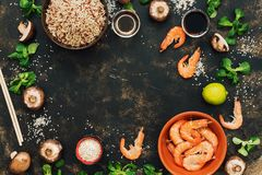 Frame with the ingredients of Asian food. Crude brown rice,shrimps, mushrooms. Copy space, top view. The concept of Asian cuisine