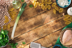 Frame of ingredients for cooking Italian pasta on wooden table Royalty Free Stock Photo
