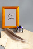 Frame, inkpot, feather, old paper on grey fabric. Wooden frame and old paper feather and inks Royalty Free Stock Images