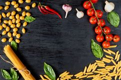 Frame of Italian traditional food, spices and ingredients for cooking as basil, cherry tomatoes, chili pepper, garlic and pasta royalty free stock images