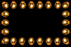 Frame of lamps. Glowing lamps on a black background. Place for text royalty free stock photo