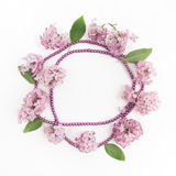 Frame with lilac flowers and leaves on white background. flat lay, overhead view stock photos