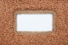 Frame made of burlap and buckwheat grains lies on white background Royalty Free Stock Photo