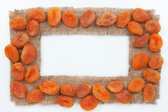 Frame made of burlap with dried apricots Royalty Free Stock Photo