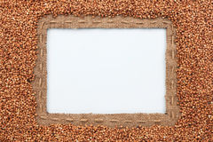 Frame made of burlap with the line and buckwheat  grain  lies on Royalty Free Stock Images