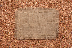 Frame made of burlap with the line lies on  buckwheat  grains Royalty Free Stock Photos