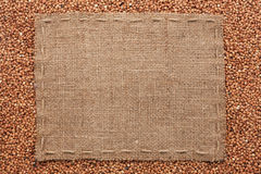 Frame made of burlap with the line lies on  buckwheat  grains Royalty Free Stock Photography