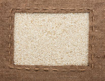 Frame made of burlap with the line lies on  rice  grains Stock Photography