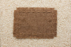 Frame made of burlap with the line lies on  rice  grains Royalty Free Stock Photography