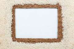 Frame made of burlap with the line and  rice  grain  lies on whi Royalty Free Stock Image