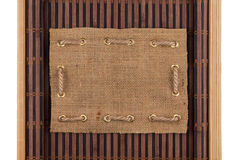 Frame made of burlap lying on a bamboo mat in the form of manuscript Stock Images