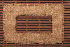 Frame made of burlap lying on a bamboo  mat Royalty Free Stock Images