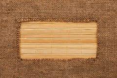 Frame made of burlap lying on a bamboo  mat Stock Image