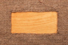 Frame made of burlap  lying on a wooden surface Stock Image
