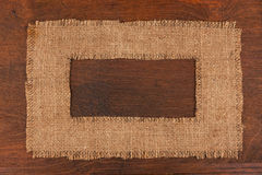 Frame made of burlap  lying on a wooden surface Royalty Free Stock Photo
