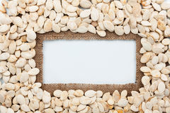 Frame made of burlap and pumpkin seeds lies on white background Stock Photo