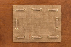 Frame made of burlap with a rope threaded through in gold rings, lie on a wooden surface Stock Photo