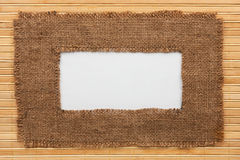Frame made of burlap with white background lying on a bamboo mat Stock Photography
