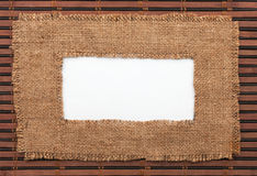 Frame made of burlap with white background lying on a bamboo mat Stock Images
