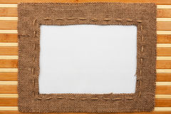 Frame made of burlap with white background lying on a bamboo mat. With space for your text stock photo
