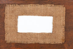 Frame made of burlap with white background lying on a wooden sur Royalty Free Stock Photos