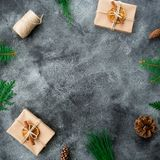 Frame made of Christmas gift boxes, winter plants and pine cones on dark background. New year composition. Flat lay. Top view Stock Photos