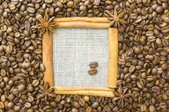 The frame is made of cinnamon , star anise , around the grain roasted coffee on a background of linen . A place for your inscripti Stock Photography