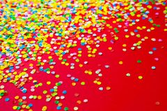 Frame made of colored confetti. Red background. Frame made of colored confetti. Red Royalty Free Stock Image