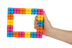 Frame made of colorful construction toy in female hand Stock Images