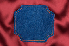 Frame made of denim fabric with yellow stitch on red silk  with space for your text Stock Photos