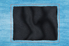 Frame made of denim fabric with yellow stitching on black silk Royalty Free Stock Image