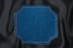 Frame made of denim fabric with yellow stitching on black silk Stock Photography