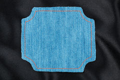 Frame made of denim fabric with yellow stitching on black silk Stock Image