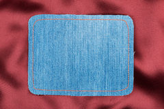 Frame made of denim fabric with yellow stitching on red silk Stock Photos