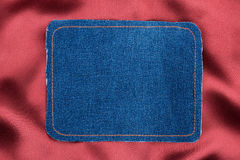Frame made of denim fabric with yellow stitching on red silk Stock Image