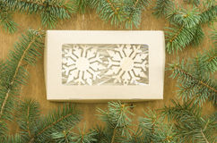 Frame made of fir branches and box with snowflakes. Royalty Free Stock Photography