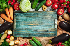 Frame made from fresh vegetables on wooden. Border composition  made with fresh vegetables on wooden rustic table with blue vintage tray. Top view, space for Royalty Free Stock Photography