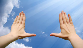 Frame made of hands at clouds and shine. Photo 1 Royalty Free Stock Photography