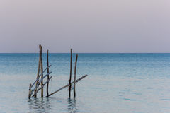 A frame made from old wooden posts stands in a calm sea at golde Royalty Free Stock Images