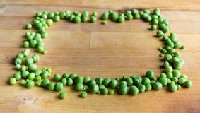 Frame made of peas. On wooden board Stock Images