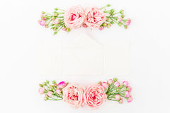 Frame made of purple roses, leaves, buds, cards and envelope on white background. Flat lay, top view. Floral pattern of pink flowe Royalty Free Stock Image