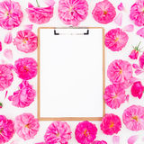 Frame made of purple roses, ranunculus and clipboard on white background. Flat lay, top view. Floral pattern of pink flowers Royalty Free Stock Image