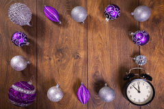 Frame made by purple and silver christmas baubles and clock Stock Images