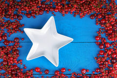 Frame made of red currant and cherry with plate Royalty Free Stock Photos