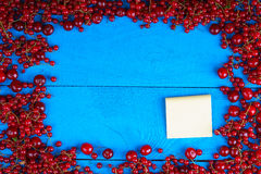 Frame made of red currant and cherry with stick note Royalty Free Stock Photos