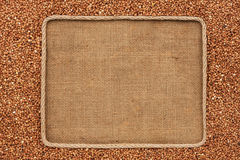Frame made of rope with  buckwheat  grains on sackcloth Stock Images
